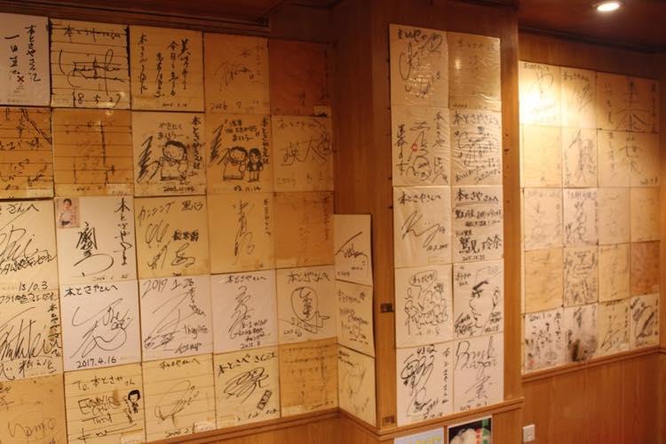 ▲所狭しと芸能人やスポーツ選手などのサインが飾られている店内の壁。